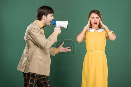Photo for Woman in vintage clothes covering ears with hands while angry man yelling in loudspeaker isolated on green - Royalty Free Image