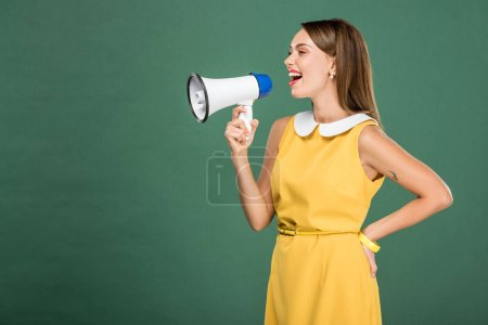 Photo for Beautiful stylish woman in yellow dress shouting in loudspeaker isolated on green with copy space - Royalty Free Image