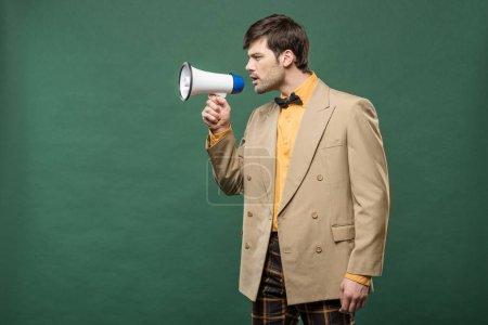 hombre guapo en ropa vintage hablando en altavoz aislado en verde con espacio de copia