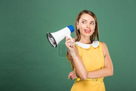 Photo for Beautiful stylish woman in yellow dress holding loudspeaker isolated on green with copy space - Royalty Free Image