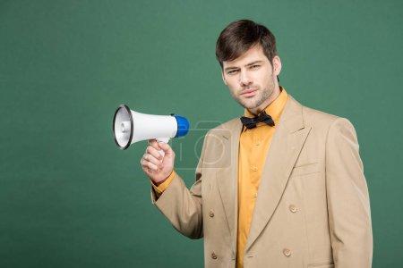 schöner Mann in Vintage-Kleidung mit Lautsprecher und Blick in die Kamera isoliert auf grün