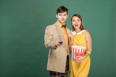 Photo pour Beau couple dans des vêtements vintage avec télécommande et pop-corn regarder film isolé sur vert - image libre de droit