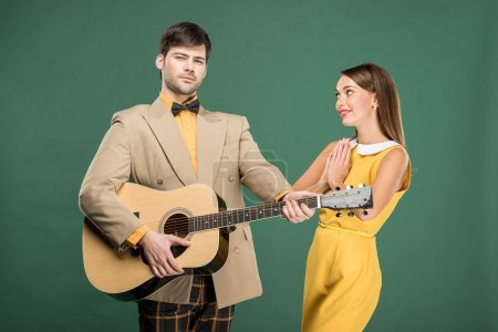 Photo for Handsome man in vintage clothes playing acoustic guitar while beautiful woman doing please gesture isolated on green - Royalty Free Image