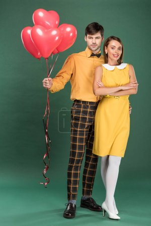 Photo for Beautiful couple with heart shaped balloons looking at camera on green background - Royalty Free Image