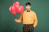 """Постер, картина, фотообои """"красавец в винтажной одежды с воздушными шарами в форме сердца, изолированные на зеленый"""""""