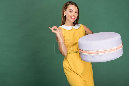 Photo for Beautiful smiling woman pointing with finger and holding macaroon model isolated on green - Royalty Free Image