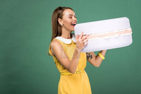 Photo for Beautiful smiling woman eating macaroon model isolated on green - Royalty Free Image