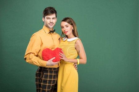 Photo pour Beau couple tenant coeur en forme de coussin et regardant la caméra isolée sur vert avec espace copie - image libre de droit