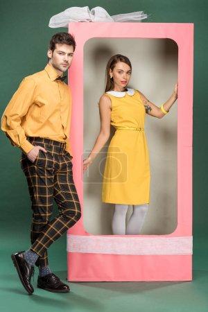 Photo pour Belle femme posant dans une boîte rose décorative avec arc tandis que bel homme en vêtements vintage regardant loin sur fond vert - image libre de droit