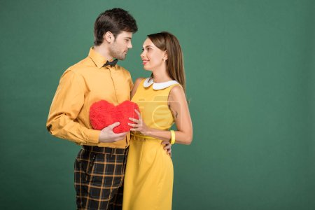 Photo for Beautiful couple holding heart shaped pillow isolated on green with copy space - Royalty Free Image
