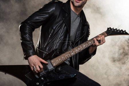 Photo pour Recadrée vue en collaboration avec veste en cuir, jouant la guitare électrique sur fond de fumée - image libre de droit