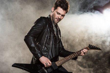 Photo pour Beau rocker en veste en cuir jouant de la guitare électrique sur fond fumé - image libre de droit