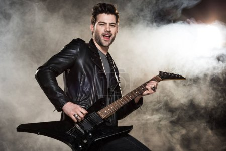 handsome rocker in leather jacket playing electric guitar on smoky background