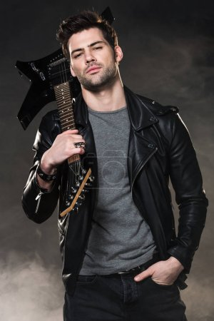 Photo for Handsome rocker holding electric guitar and looking at camera on dark smoky background - Royalty Free Image