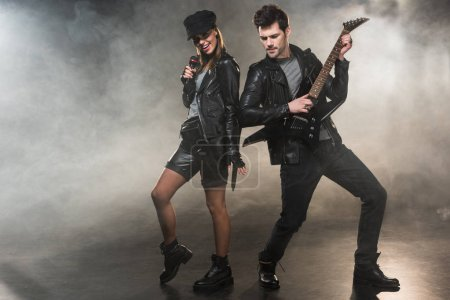 woman in leather jacket singing while man playing electric guitar on smoky background