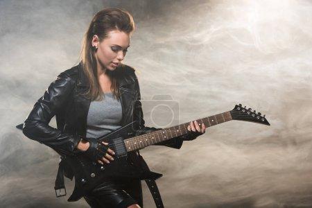 Photo pour Belle femme en veste de cuir, jouant la guitare électrique sur fond de fumée - image libre de droit