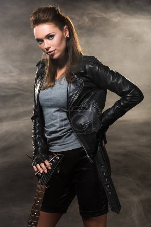 beautiful woman in leather jacket posing with electric guitar on smoky background