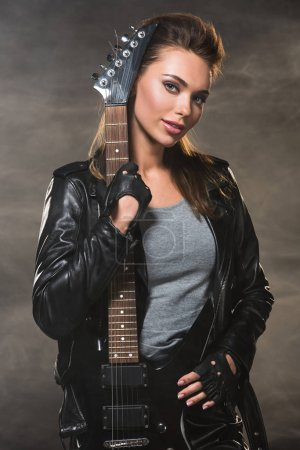 beautiful woman in leather jacket looking at camera and posing with electric guitar on smoky background