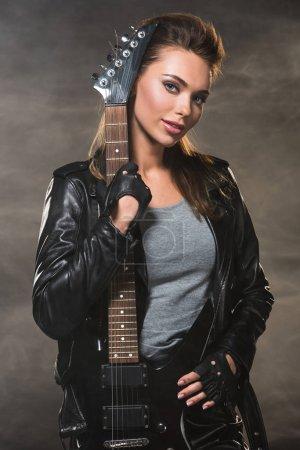 schöne Frau in Lederjacke blickt in die Kamera und posiert mit E-Gitarre auf rauchigem Hintergrund