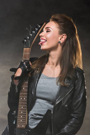 beautiful woman in leather jacket sticking tongue out and posing with electric guitar on dark background