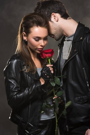 Photo for Beautiful couple in leather jackets posing with red rose on dark background - Royalty Free Image