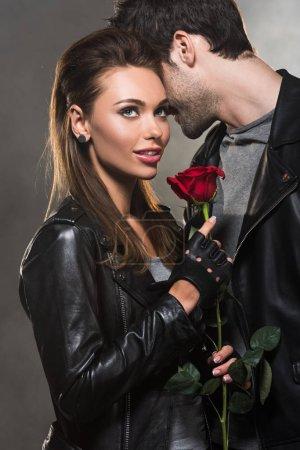 Photo pour Beau couple en vestes de cuir, posant avec une rose rouge sur fond gris - image libre de droit