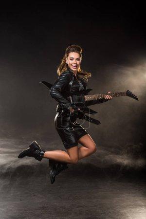 hermosa mujer en chaqueta de cuero mirando a la cámara y saltando con la guitarra eléctrica sobre fondo ahumado