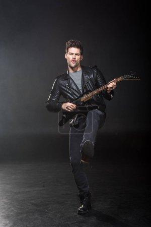 Photo pour Beau rocker en blouson de cuir, jouant la guitare électrique sur fond noir - image libre de droit