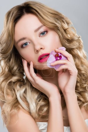 young blonde gentle woman holding purple orchid in hand while touching face isolated on grey