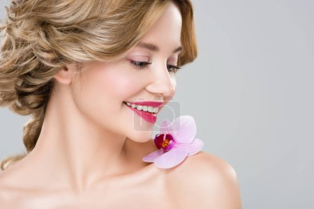 young smiling naked woman with purple orchid on shoulder isolated on grey
