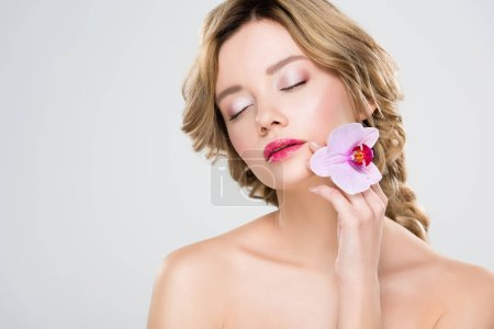 girl with closed eyes holding flower isolated on grey