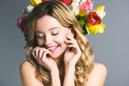 smiling girl with wreath of flowers on hair isolated on grey