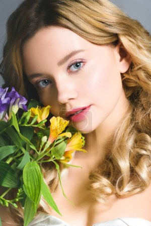 attractive blonde young woman with flowers looking at camera