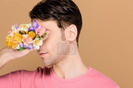 Foto de Cubierta la cara con las flores de alstroemeria en mano del hombre aislado en beige - Imagen libre de derechos