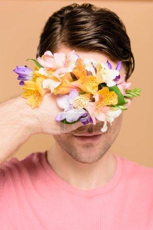 Foto de Hombre sonriente que cubre la cara con las flores de alstroemeria en mano aislado en beige - Imagen libre de derechos