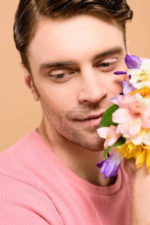 Foto de Hombre sonriente cerca flores de alstroemeria aislado en beige - Imagen libre de derechos