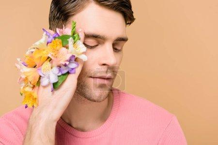 Foto de Hombre hermoso con las flores de alstroemeria en mano aislado en beige - Imagen libre de derechos