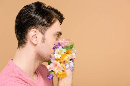 Foto de Hombre que cubre la boca con flores aisladas en beige - Imagen libre de derechos