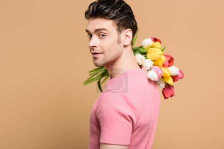 Photo for Happy man holding bouquet of flowers on shoulder isolated on beige - Royalty Free Image