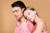 beautiful  woman with flowers on face hugging man isolated on beige