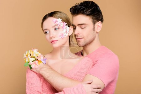 Photo for Handsome man embracing attractive girlfriend with flowers on face isolated on beige - Royalty Free Image