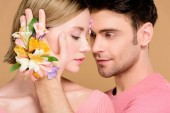 handsome man touching face of beautiful girlfriend with flowers on face isolated on beige