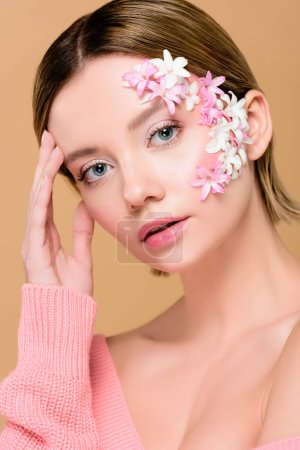 beautiful woman with flowers on face looking at camera isolated on beige