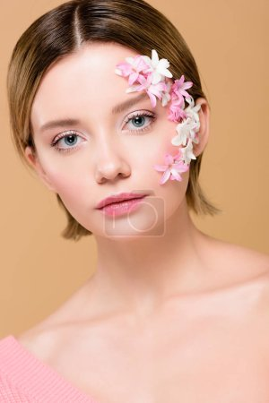 Photo for Beautiful girl with flowers on face looking at camera isolated on beige - Royalty Free Image