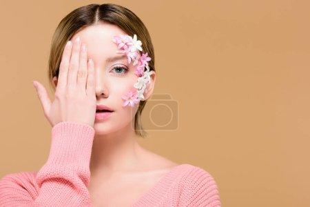 Photo pour Jolie femme avec des fleurs sur le visage couvrant un oeil avec la main isolé sur beige - image libre de droit