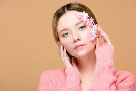 elegant girl with flowers on face looking at camera isolated on beige
