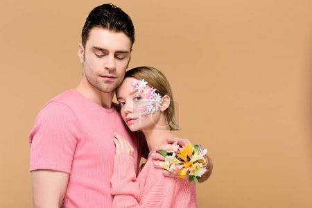 Photo for Handsome man with closed eyes embracing attractive girlfriend with flowers on face isolated on beige - Royalty Free Image
