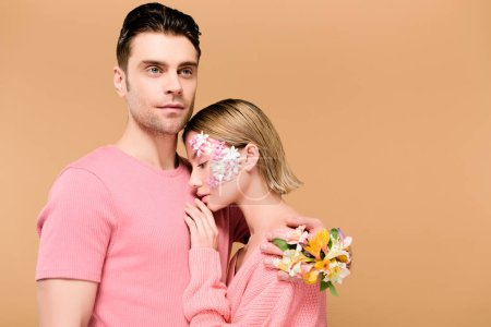Photo for Handsome boyfriend embracing beautiful girlfriend with flowers on face isolated on beige - Royalty Free Image