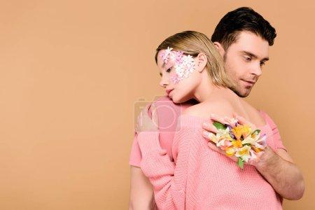 Foto de Hombre hermoso con las flores de alstroemeria en novia abraza de mano con flores en la cara aislado en beige - Imagen libre de derechos