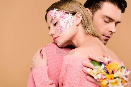Foto de Novio con flores de alstroemeria en abrazar novia atractiva de mano con flores en la cara aislado en beige - Imagen libre de derechos